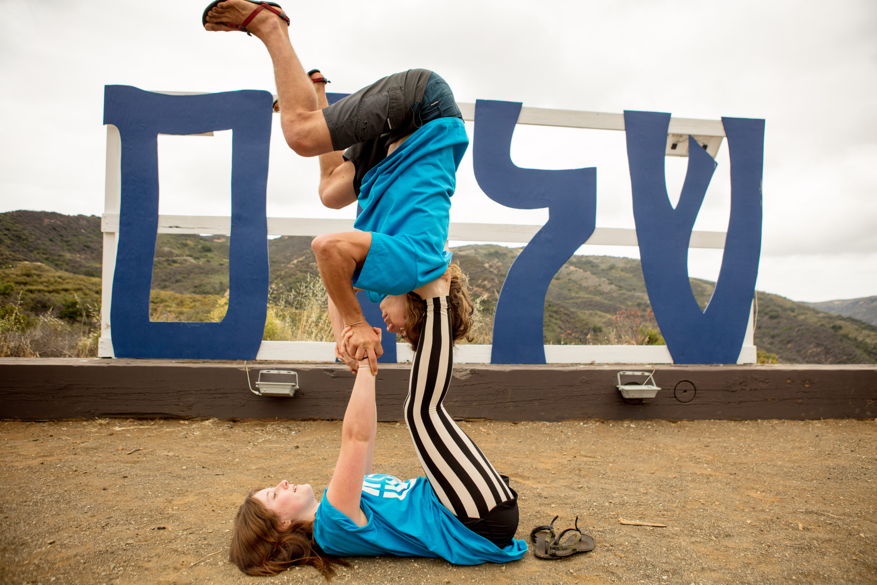 Two Friends Doing Yoga in Front of Shalom Sign