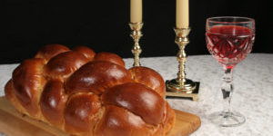 A table set for Shabbat with challah bread, candlesticks and wine.  Black background, complete view.